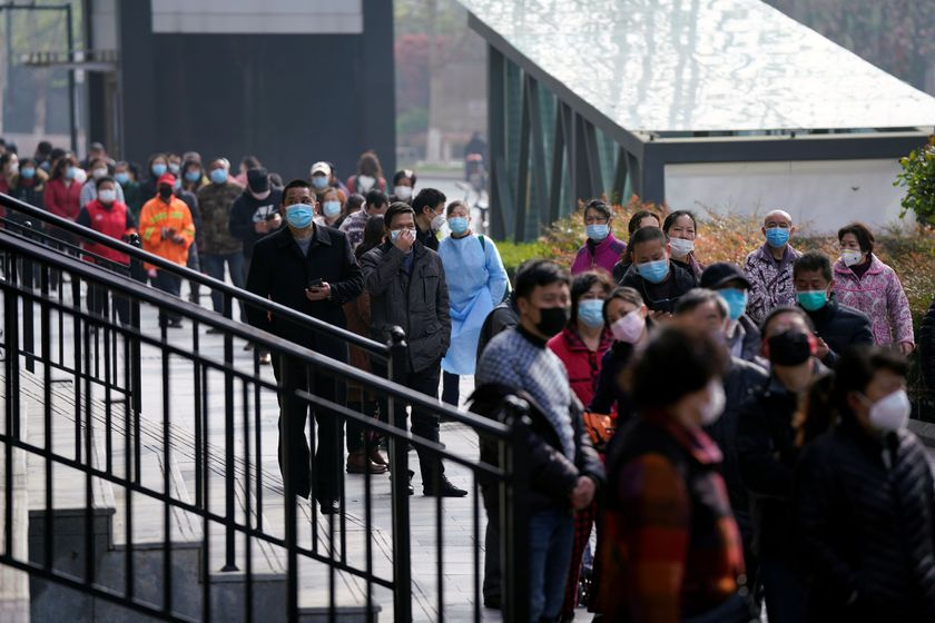 People wearing face masks line up to enter a supermarket in Wuhan