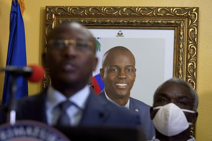 """A picture of late Haitian President Jovenel Moise hangs on the wall of his former residence, behind interim Prime Minister Claude Joseph giving a press conference in Port-au-Prince, Tuesday, July 13, 2021. Authorities in Haiti on Thursday forcefully pushed back against reports that current government officials were involved in the July 7 killing of Haitian President Jovenel Moïse, calling them """"a lie."""" (AP Photo/Joseph Odelyn)"""
