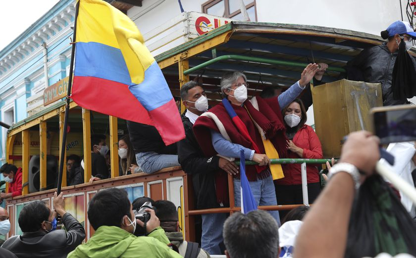 """Former banker Guillermo Lasso, presidential candidate for the CREO political party, and his wife Maria de Lourdes Alcivar greet supporters from a """"Chiva,"""" an old truck converted to carry tourists, during a rally ahead of Ecuador's runoff presidential election in Quito, Ecuador, Wednesday, April 7, 2021. (AP Photo/Dolores Ochoa)"""