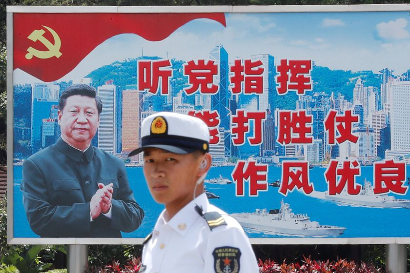 FILE PHOTO: People's Liberation Army Navy soldier stands in front of a backdrop featuring Chinese President Xi Jinping during an open day of Stonecutters Island naval base, in Hong Kong