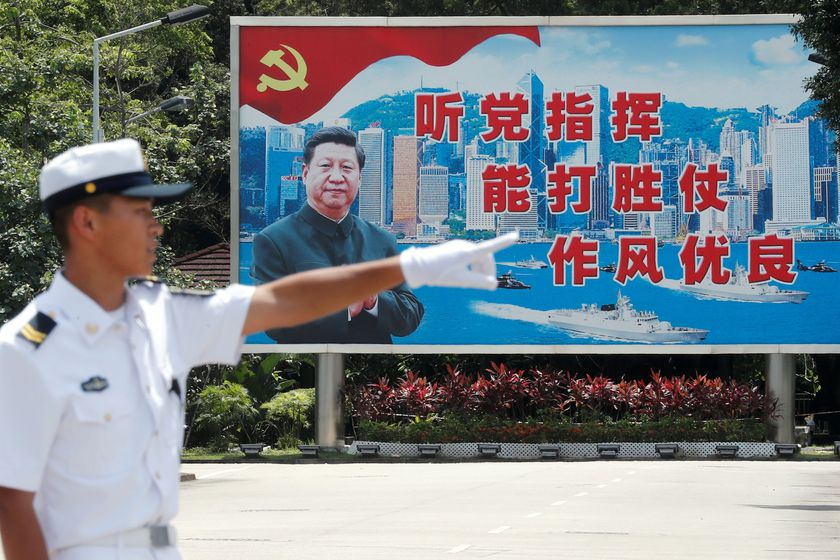 FILE PHOTO: A People's Liberation Army Navy soldier stands in front of a backdrop featuring Chinese President Xi Jinping during an open day of Stonecutters Island naval base, in Hong Kong