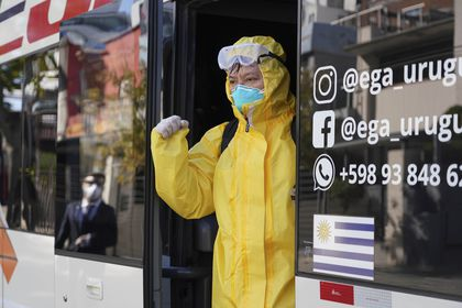 A crew member from the Australian cruise ship Greg Mortimer gets dropped off at a hotel in Montevideo, Uruguay, Tuesday, May 12, 2020. Their ship has been anchored off the coast since March 27 and today the crew, some infected with the new coronavirus, will quarantine at two hotels. (AP Photo/Matilde Campodonico)