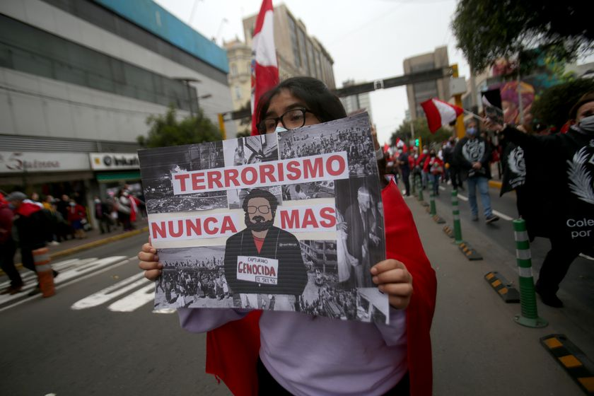12 September 2021, Peru, Lima: A woman carries a placard describing Peruvian guerrilla leader Guzman as a mass murderer at a demonstration marking his death. Abimael Guzman, the former leader of the Peruvian guerrilla organization Shining Path (Sendero Luminoso), died at the age of 86 in a maximum-security prison, the prison administration announced on Saturday. Almost 70,000 people were killed in clashes between the Sendero Luminoso and state security forces between 1980 and 2000. Photo: Cesar Lanfranco/dpa 12/09/2021 ONLY FOR USE IN SPAIN
