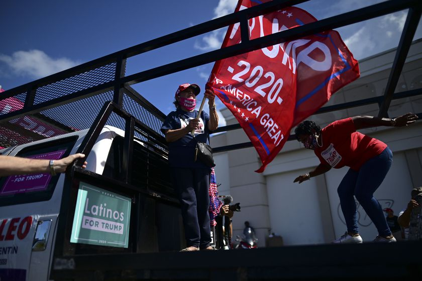 Former senator Miriam Ramírez de Ferrer carries a pro-Trump flag moments before leaving for the headquarters of the Republican party in support of President Donald Trump's candidacy a few weeks before the presidential election next November, in Carolina, Puerto Rico, Sunday, Oct. 18, 2020. President Donald Trump and former Vice President Joe Biden are targeting Puerto Rico in a way never seen before to gather the attention of tens of thousands of potential voters in the battleground state of Florida. (AP Photo/Carlos Giusti)