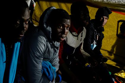 Migrants rest onboard the Proactiva Open Arms NGO rescue boat, sailing the Mediterranean Sea towards the Italian port of Taranto