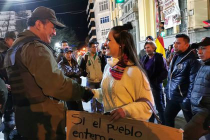 An university student and police guard shake hands during a protest in Oruro, Bolivia