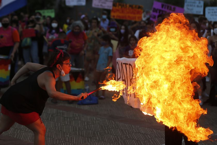 """A fire breather burns a poster with the word """"Patriarchy"""" during a march commemorating Women's International Day in Asuncion, Paraguay, Monday, March 8, 2021. (AP Photo/Jorge Saenz)"""