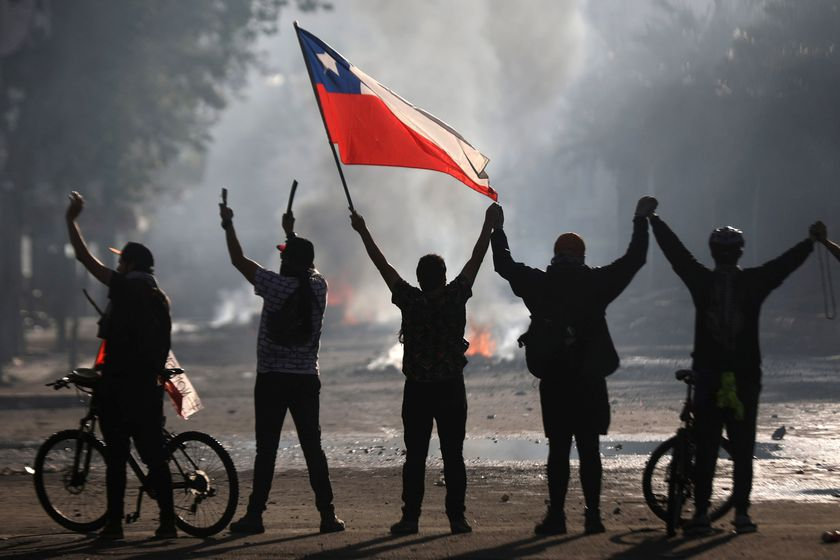 A demonstrator holds a Chilean flag during a protest against Chile's state economic model in Santiago October 21, 2019. REUTERS/Edgard Garrido