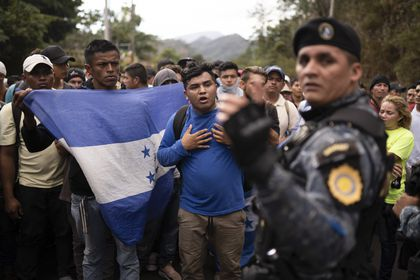 FILE - In this Jan. 16, 2020 file photo, Honduran migrants walking in a group stop before Guatemalan police near Agua Caliente, Guatemala, on the border with Honduras. In a report released Tuesday, Oct. 13, 2020, by the Democratic staff of a U.S. Senate committee says U.S. immigration agents assigned to Guatemala to advise local authorities violated terms of their funding by helping officials deport Hondurans traveling in a migrant caravan early this year. (AP Photo/Santiago Billy, File)