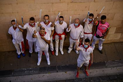 A group of would be participants wear face masks and sing a song along the route of the running of the bulls of the San Fermin festival, which was canceled this year due to the conoravirus, in Pamplona, northern Spain, Tuesday, July 7, 2020. (AP Photo/Alvaro Barrientos)