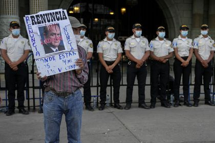 A protestors holds a sign with a portrait of Guatemalan President Alejandro Giammattei outside the National Palace as people attend a rally in support of anti-corruption prosecutor Juan Francisco Sandoval, in Guatemala City, Saturday, July 24, 2021. Sandoval fled Guatemala late Friday, arriving in neighboring El Salvador just hours after he was removed from his post. (AP Photo/Moises Castillo)