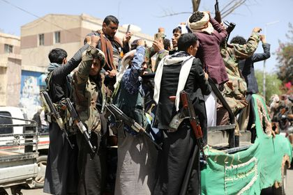 Armed Houthi followers ride on the back of a truck outside a hospital in Sanaa