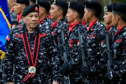 FILE PHOTO: Philippine President Rodrigo Duterte, wearing a military uniform, reviews scout ranger troops upon his arrival during the 67th founding anniversary of the First Scout Ranger regiment in San Miguel town, Bulacan province, north of Manila