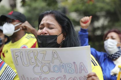 A woman cries as she sings the Colombian national anthem, during a demonstration outside Colombia's embassy in Quito, Ecuador, Tuesday, May 4, 2021. The demonstration is in support of the protests going on in Colombia over the tax reform proposal by the government that has left several dead in that country. (AP Photo/Dolores Ochoa)