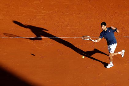 FILE PHOTO: Serbia's second seed Novak Djokovic plays a shot to Pablo Carreno Busta during his three-set victory over the Spaniard in the third round of the Monte Carlo Masters.