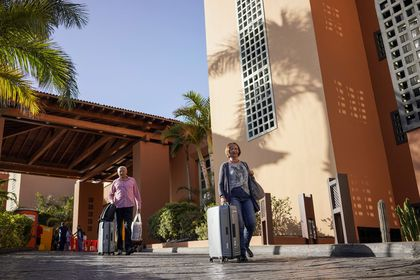 Tourists carry their belongings as they leave the H10 Costa Adeje Palace hotel, after their quarantine was lifted, following the coronavirus outbreak in Adeje