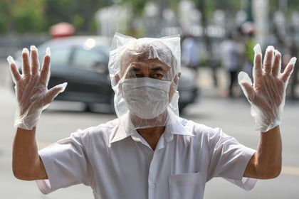 A man wearing a plastic bag as precaution against the coronavirus disease (COVID-19), takes part in protests demanding to reduce the Royal budget and distribute it to people, in front of the government house in Bangkok, Thailand January 26, 2021. REUTERS/Challinee Thirasupa