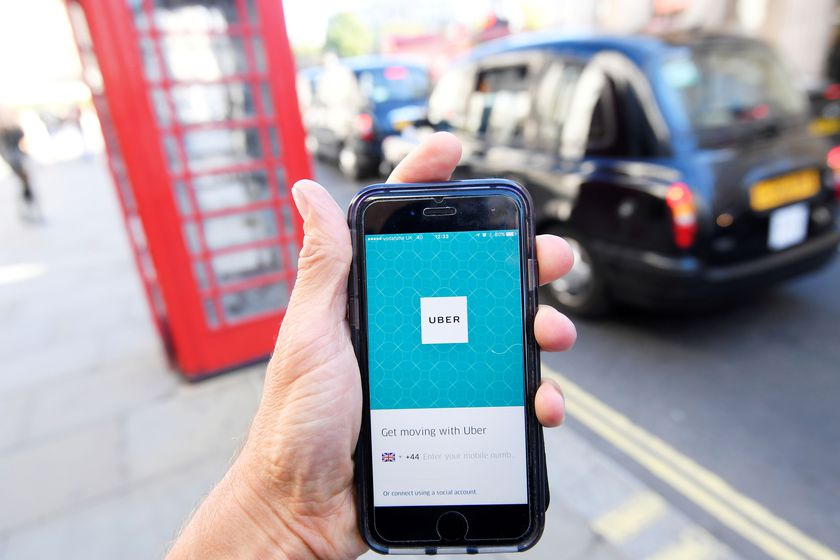 FILE PHOTO: A photo illustration shows a London taxi passing as the Uber app logo is displayed on a mobile telephone, as it is held up for a posed photograph in central London