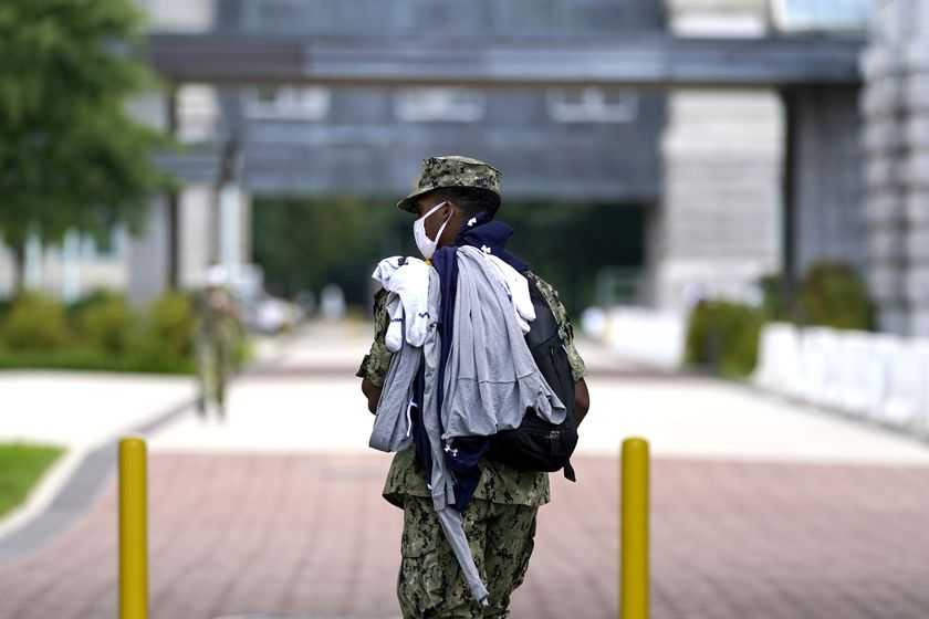 A midshipman wears a face mask to protect against COVID-19 while walking with laundry at the U.S. Naval Academy, Monday, Aug. 24, 2020, in Annapolis, Under the siege of the coronavirus pandemic, classes have begun at the Naval Academy, the Air Force Academy and the U.S. Military Academy at West Point. But unlike at many colleges around the country, most students are on campus and many will attend classes in person. Md. (AP Photo/Julio Cortez)