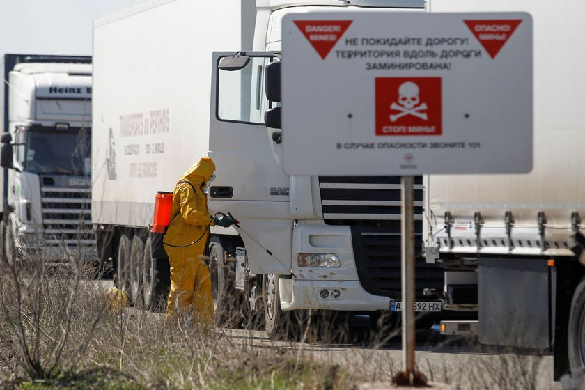 Specialists sanitize a truck convoy of the International Committee of the Red Cross at a check point in Donetsk region