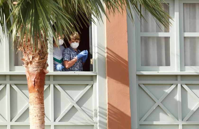 Guests, wearing protective face masks, look out from a window at H10 Costa Adeje Palace, which is on lockdown after cases of coronavirus have been detected there in Adeje