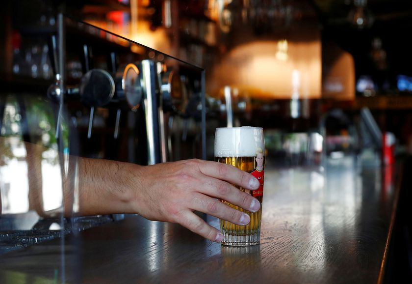 Bar owner tests a protective plexiglass screen installed on the counter, in Brussels