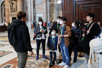 Tourists wearing protective face masks visit the St. Peter's Basilica, after the Vatican reports its first case of coronavirus, at the Vatican