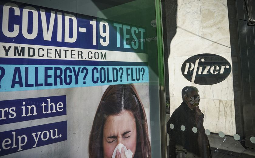 A bus stop ad for COVID-19 testing is shown outside Pfizer world headquarters in New York on Monday Nov. 9, 2020. Pfizer says an early peek at its vaccine data suggests the shots may be 90% effective at preventing COVID-19, but it doesn't mean a vaccine is imminent. (AP Photo/Bebeto Matthews)