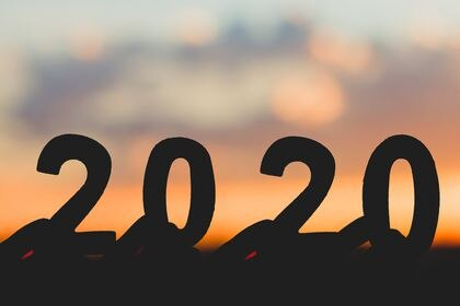 Silhouette 2020 Happy New Year of Hand holding wooden number on  sky and cloud twilight beautiful nature background.