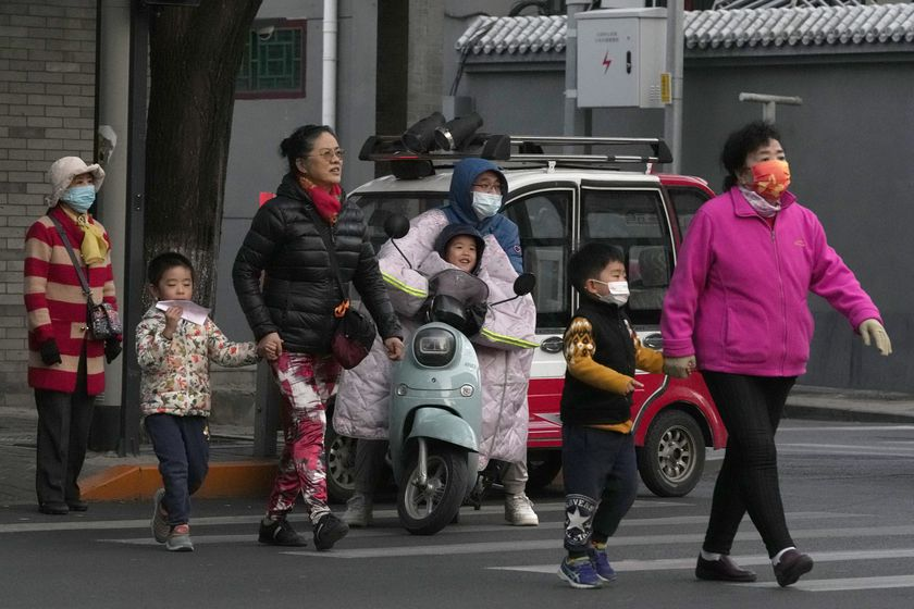Residents, some wearing masks, cross a road in Beijing, China, Wednesday, Oct. 20, 2021. China's capital Beijing has begun offering booster shots against COVID-19, four months before the city and surrounding regions are to host the Winter Olympics. (AP Photo/Ng Han Guan)