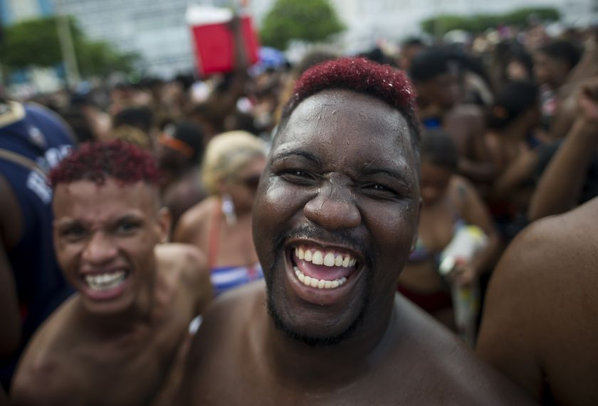 """FILE - in this Jan. 12, 2020 file photo, revelers smile as they look on the camera during the """"Bloco da Favorita"""" street party on Copacabana beach, Rio de Janeiro, Brazil. The city announced on Thursday, Sept. 24, said it has delayed its annual Carnival parade, saying the global spectacle cannot go ahead in February because of Brazil's continued vulnerability to the new coronavirus pandemic, but has yet to announce a decision about the Carnival street parties that take place across the city.  (AP Photo/Bruna Prado, File)"""