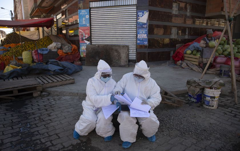 Healthcare workers dressed in full protective gear organize their documents of data they have collected during a house-to-house new coronavirus testing drive, ringed by a produce market in the Villa Dolores neighborhood of El Alto, Bolivia, Saturday, July 18, 2020. (AP Photo/Juan Karita)