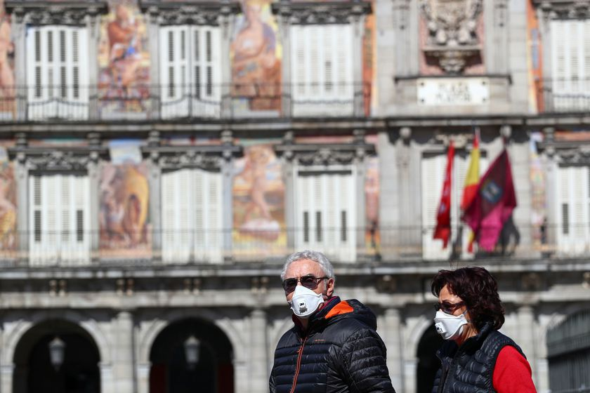 A couple wear protective face masks as they walk at one of the main touristic landmarks Plaza Mayor in Madrid