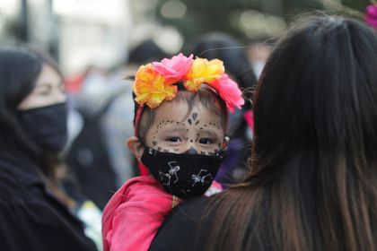 A child wears a face mask as women protest on the Day of the Dead against gender violence and femicide, in Mexico City, Mexico, November 2, 2020. REUTERS/Raquel Cunha