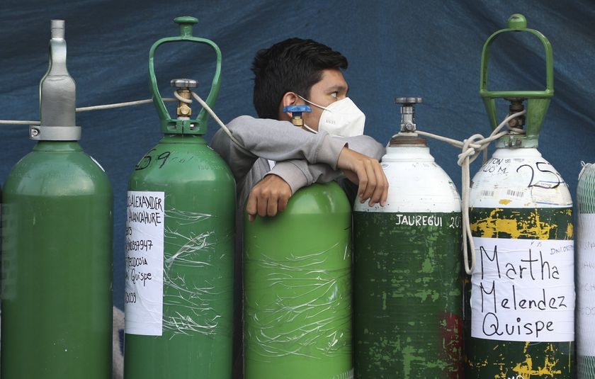 A man leans on his empty oxygen cylinder waiting for a refill shop to open in the San Juan de Lurigancho neighborhood of Lima, Peru, Monday, Feb. 22, 2021, as the lack of medical oxygen to treat COVID-19 patients continues to be the norm nationwide. Long lines form outside private providers with many spending the night outside so as to not lose their place in line. (AP Photo/Martin Mejia)