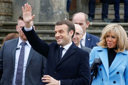 French President Emmanuel Macron waves as he leaves with his wife Brigitte Macron, after casting their ballots, during the first round of the mayoral elections in Le Touquet