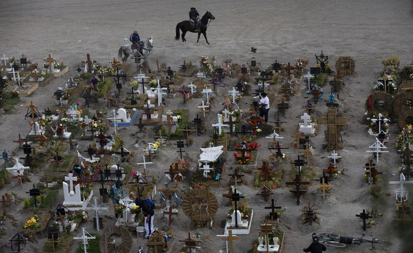 Workers ride their horses in the Valle de Chalco municipal cemetery, usually reserved to bury COVID-19 victims, on the outskirts of Mexico City, Wednesday, Nov. 18, 2020. Mexico topped 1 million registered coronavirus cases and nearly 100,000 test-confirmed deaths over the last week, though officials agree the number is probably much higher. (AP Photo/Marco Ugarte)