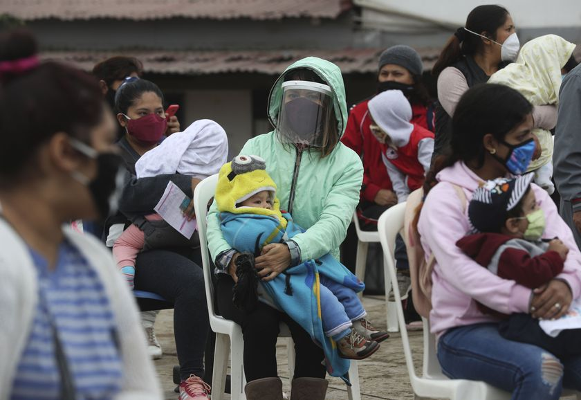 Women hold their children as they wait to vaccinate them during a vaccination campaign in the Villa El Salvador neighborhood of Lima, Peru, Friday, June 26, 2020. In an attempt to strengthen primary health care for vulnerable populations in the country, the Ministry of Health has increased services. (AP Photo/Martin Mejia)