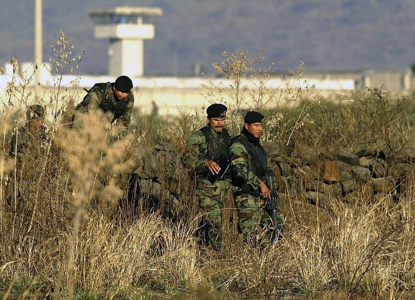 "FILE - In this Jan. 28, 2005 file photo, Mexican Army soldiers inspect the surrounding the top-security Puente Grande prison, on the outskirts Guadalajara City, Mexico. The Mexican government announced Monday, Sept. 28, 2020, that it will close the Puente Grande federal prison made famous by the 2001 escape of convicted drug lord Joaquin ""El Chapo"" Guzman. (AP Photo/Guillermo Arias, File)"