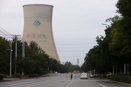 FILE PHOTO: A person walks near a China Energy coal-fired power plant in Shenyang, Liaoning province, China September 29, 2021. REUTERS/Tingshu Wang/File Photo