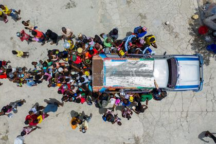 People gather around a car where volunteers distribute food to refugees at a shelter for families displaced by gang violence at the Saint Yves Church in Port-au-Prince, Haiti July 26, 2021. REUTERS/Ricardo Arduengo     TPX IMAGES OF THE DAY