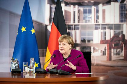 A handout picture shows German Chancellor Angela Merkel talking to French President Emmanuel Macron during a joint video conference in the chancellery in Berlin