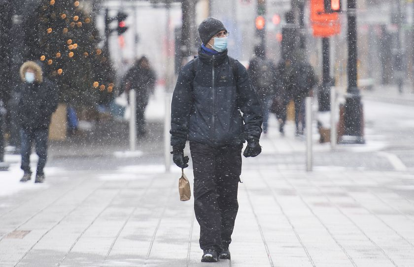 A man wears a face mask as he walks along Sainte-Catherine Street on Boxing Day in Montreal, Saturday, Dec. 26, 2020, as the COVID-19 pandemic continues in Canada and around the world. (Graham Hughes/The Canadian Press via AP)