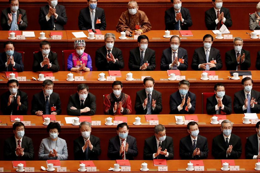 Chinese officials applaud at the closing session of NPC in Beijing