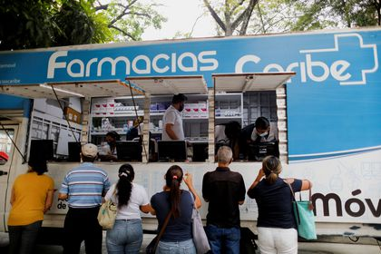 People buy medicines from a pharmacy truck amid a spike in infections of the coronavirus disease (COVID-19) that has led the government to extend lockdown measures, in Caracas, Venezuela April 6, 2021.  REUTERS/Leonardo Fernandez Viloria NO RESALES. NO ARCHIVES