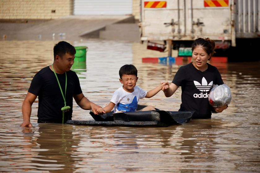 A child sits on a makeshift raft on a flooded road following heavy rainfall in Zhengzhou, Henan province, China July 22, 2021.  REUTERS/Aly Song