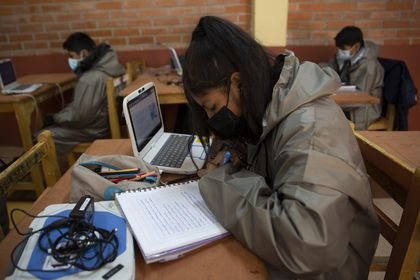 Students wearing masks to curb the spread of the new coronavirus take online classes with computers loaned to them by the teachers of the Gualberto Villarroel school in La Paz, Bolivia, Wednesday, May 12, 2021. The school's teachers and some parents are providing the devices to students who do not have access to the internet or a computer, or a cell phone to attend classes online. The school itself provides the internet signal. (AP Photo/Juan Karita)