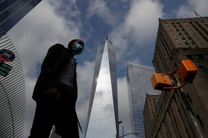 A man wearing a protective face mask walks by One World Trade Center two days before the 19th anniversary of the 9/11 attacks, amid the coronavirus disease (COVID-19) pandemic, in the lower section Manhattan, New York City