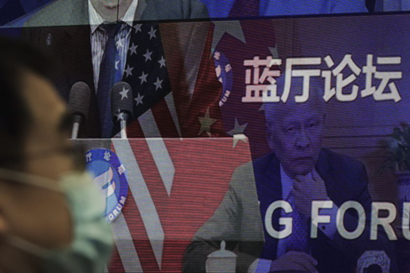 A man wearing a face mask to help curb the spread of the coronavirus sits near a screen showing delegates attend for the Lanting Forum on bringing China-U.S. relations back to the right track which chaired by Chinese Foreign Minister Wang Yi at the Ministry of Foreign Affairs office in Beijing on Monday, Feb. 22, 2021. Wang called on the U.S. Monday to lift restrictions on trade and people-to-people contacts while ceasing what Beijing considers unwarranted interference in the areas of Taiwan, Hong Kong, Xinjiang and Tibet. (AP Photo/Andy Wong)