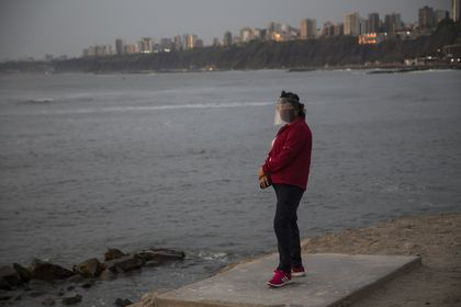 A woman wearing a mask and face shield to curb the spread of the new coronavirus stands on a platform overlooking the Pacific Ocean in Chorrillos, Lima, Peru, Tuesday, Jan. 26, 2021. (AP Photo/Rodrigo Abd)